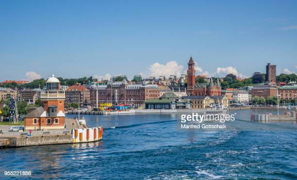 the baltic sea coastal city of helsingborg with view of the harbour lighthouse and the prominent towers of the helsingborg city hall and the karnan medieval fortress, scania, sweden - helsingborg stock pictures, royalty-free photos & images