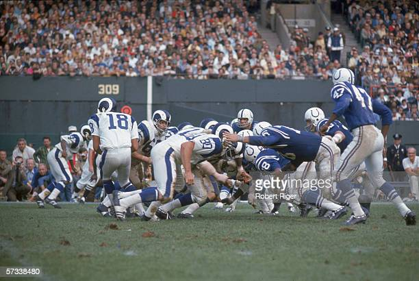 The Baltimore Colts defense goes after the Los Angeles Rams offensive line after Rams quarterback American football player Roman Gabriel hands off...
