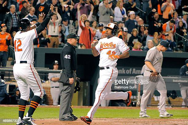 The Baltimore Orioles' Adam Jones, left, welcomes Delmon Young, who scored on a double by Chris Davis off New York Yankees relief pitcher Justin...
