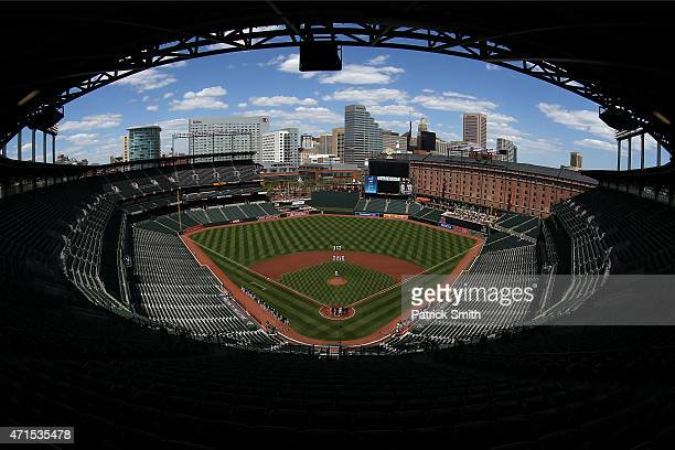 The Baltimore Orioles and Chicago White Sox stand for the nation anthem at an empty Oriole Park at Camden Yards on April 29 2015 in Baltimore...