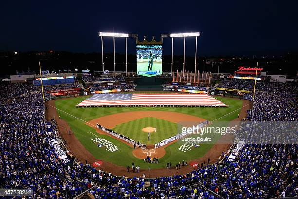 The Baltimore Orioles and the Kansas City Royals stand on the baseline during the national anthem prior to Game Three of the American League...