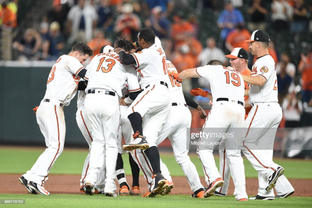 The Baltimore Orioles celebrates a Jonathan Schoop #6 of the Baltimore Orioles walk off hit in the ninth inning during a baseball game against the New York Yankees at Oriole Park at Camden Yards on July 10, 2018 in Baltimore, Maryland.