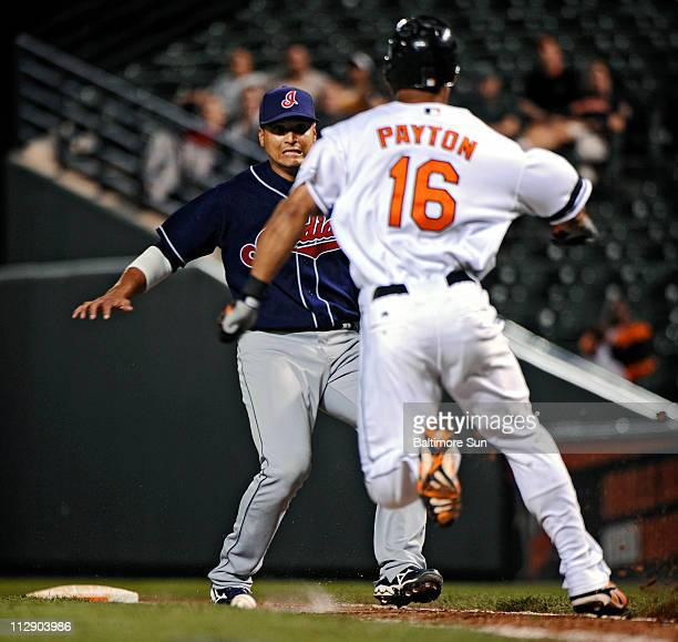 The Baltimore Orioles' Jay Payton right rans around Cleveland Indians first baseman Victor Martinez and the ball to reach frst base safely on a ball...