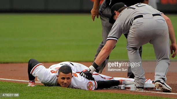 The Baltimore Orioles' Manny Machado bellyflops into third base for a triple under a late throw to Chicago White Sox third baseman Conor Gillaspie...