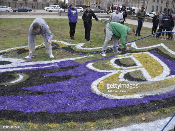 The Baltimore Ravens' grounds crew paints the team's logo outside City Hall on January 10 before a playoff game against the Tennessee Titans