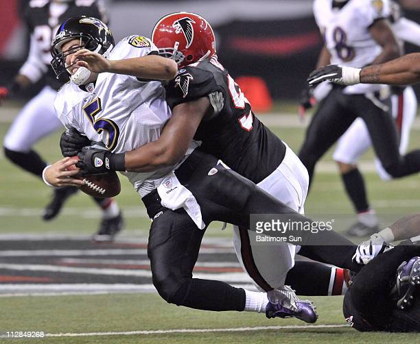 The Baltimore Ravens' Joe Flacco is brought down by the Atlanta Falcons' Vance Walker while trying for yardage on a third-down play in the first...