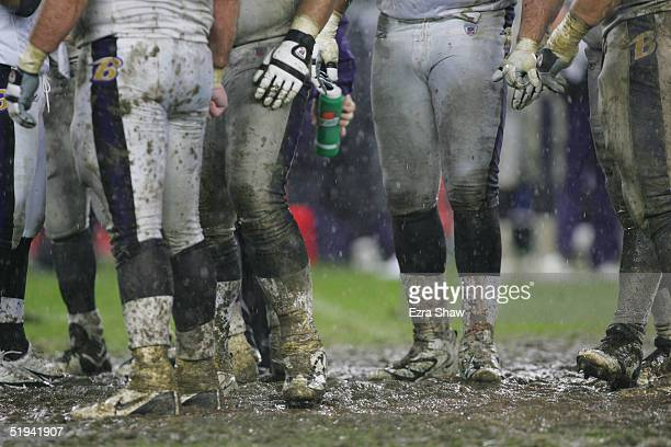 The Baltimore Ravens offense stands muddied on the rain soaked field during the game against the New England Patriots on November 28 2004 at Gillette...