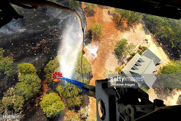 the bambi bucket attached to a ch-47 chinook helicopter, dumps water on a wildfire in texas. - 危機管理 ストックフォトと画像