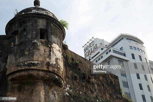 The Banco Popular building right stands near a section of the wall that surrounds Old San Juan Puerto Rico on Friday May 29 2015 For the hedge funds...