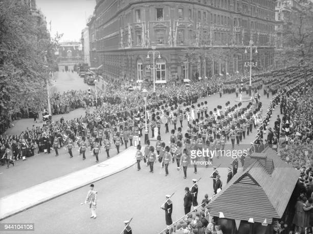 The Band and Corps of Drums of the Welsh and Irish Guards march down Northumberland Avenue ahead of the gold state coach carrying the Queen to...