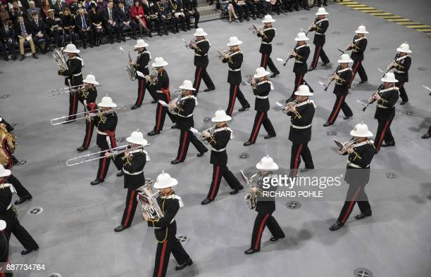 The band of the Royal Marines march onto the hangar deck during the Commissioning Ceremony for the Royal Navy aircraft carrier HMS Queen Elizabeth at...