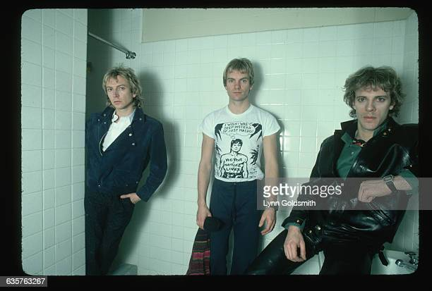 The band The Police stand in a white-tiled bathroom.