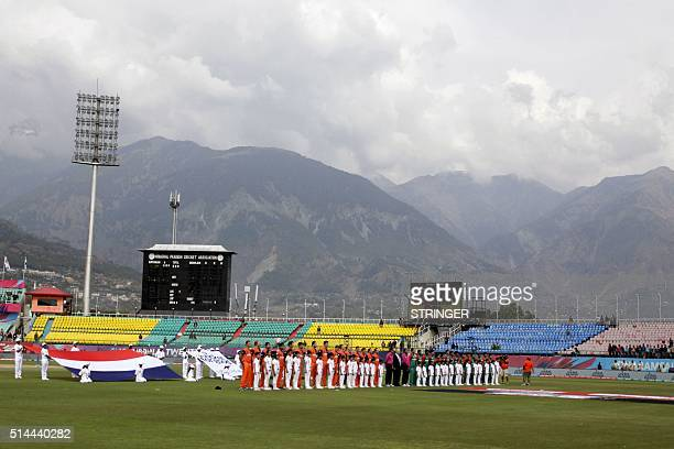The Bangladesh and Netherlands cricket teams stand for the playing of the national anthems before their World T20 game at the Himachal Pradesh...