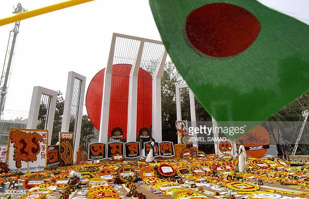 The Bangladesh flags flies over two women as they use flowers to decorate the Central Language Martyr's Memorial in Dhaka 21 February 2004 Tens of...