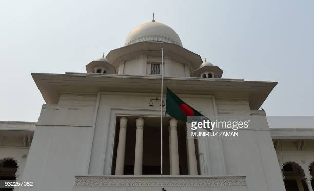 The Bangladeshi national flag is seen flown at half mast outside the High Court Building in Dhaka on March 15 as a gesture of mourning for victims of...