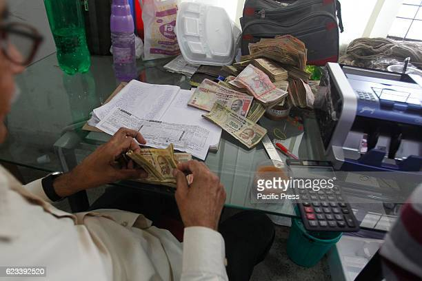 The bank employees count notes deposit by people to exchange or deposit his old high denomination banknotes in a bank