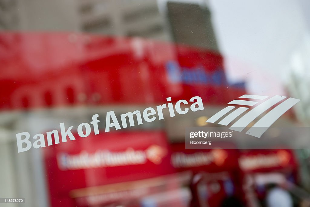 The Bank of America Corp. logo is displayed on the window of a branch in New York, U.S., on Wednesday, July 18, 2012. Bank of America Corp., the second- biggest U.S. lender, plans to trim $3 billion in annual expenses from investment banking, trading and wealth-management units. Photographer: Scott Eells/Bloomberg via Getty Images