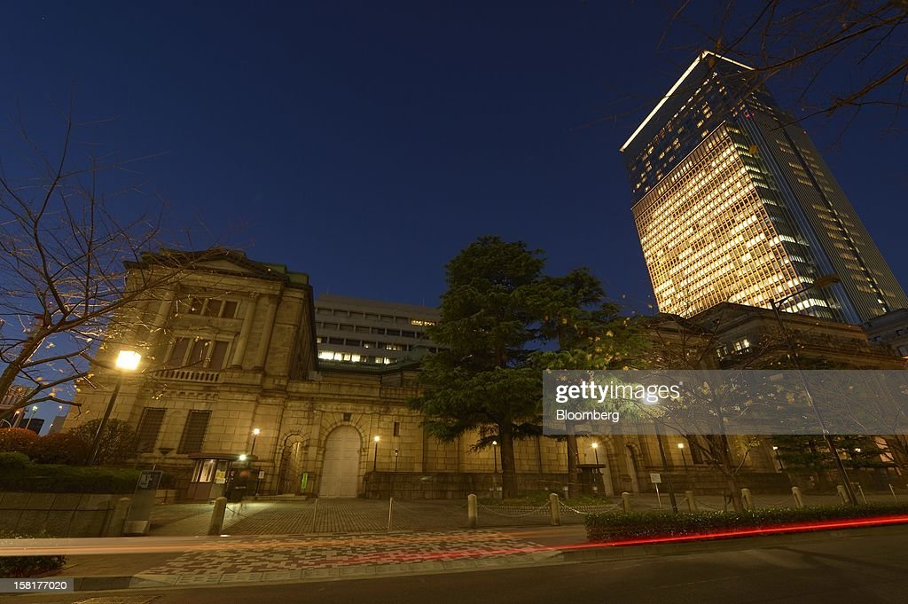 The Bank of Japan headquarters, front, stands at night in Tokyo, Japan, on Monday, Dec. 10, 2012. Japan's bond market is signaling concern that a government run by Shinzo Abe will ramp up spending to revive growth, adding to a debt burden already twice the size of the nation's economy. Photographer: Akio Kon/Bloomberg via Getty Images