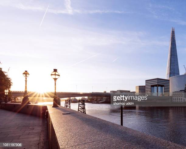 the bank of river thames and the city skyline at sunrise - london bridge stock photos and pictures
