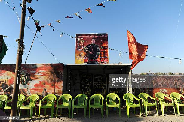 The banner of an Iraqi Shiit militiaman killed in battle fighting the Islamic State stand above a tea stall, as Iraqi Shiites prepare the route for...