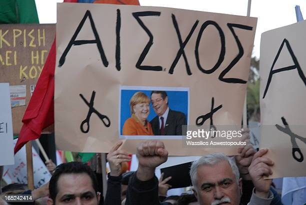 The banner shows chancellor Angela Merkel and President Nikos Anastasiadis protesters demonstrating against the bank levy in Cyprus which took place...