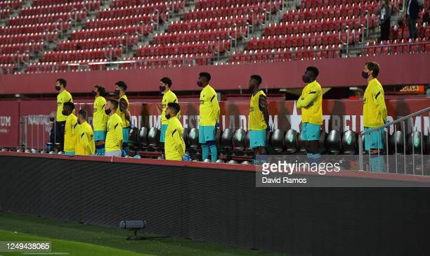 The Barcelona substitutes stand for a minutes silence in memory of the victims of the Covid-19 Pandemic prior to the La Liga match between RCD...
