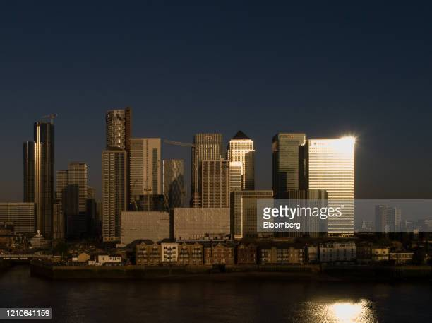The Barclays Plc headquarter office building reflects morning sunlight as it stands in the Canary Wharf financial business and shopping district in...