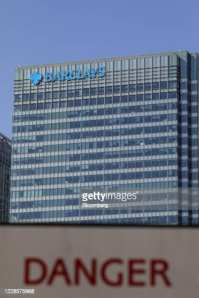The Barclays Plc office headquarters office building stands in view of a sign that read Danger in the Canary Wharf business financial and shopping...