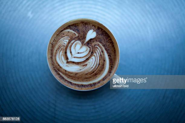 The barista fills coffee and milk froth in the cup and makes it look like the texture of a leaf in a cafe in Ginza