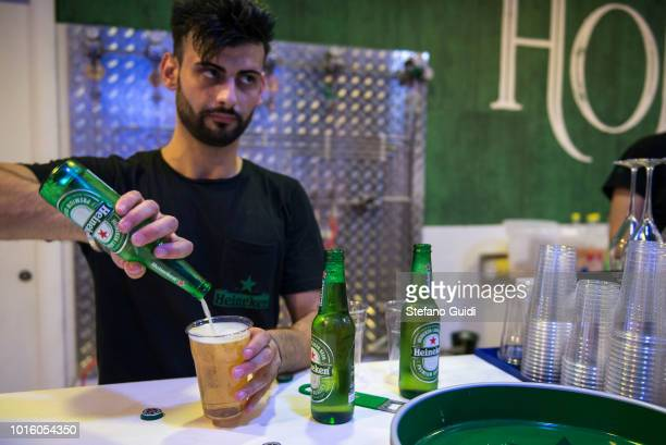 The bartender prepares a beer for customers at the counter during the nightlife in the Via Marina The Via Marina of Reggio Calabria consists of the...