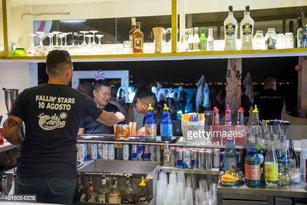 The bartender prepares cocktails for customers at the counter during the nightlife in the Via Marina The Via Marina of Reggio Calabria consists of...