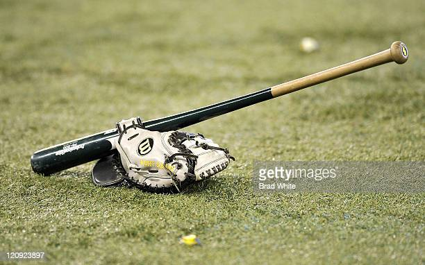 The baseball glove and bat of Kurt Suzuki of the Oakland Athletics sits on the field prior to MLB game action against the Toronto Blue Jays August 9...
