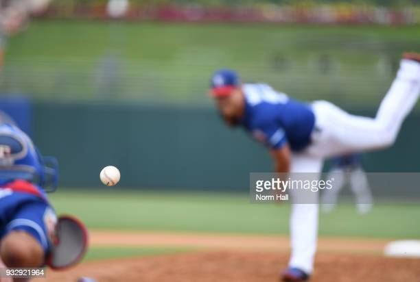 The baseball is seen as Matt Moore of the Texas Rangers delivers a third inning pitch during a spring training game against the Seattle Mariners at...