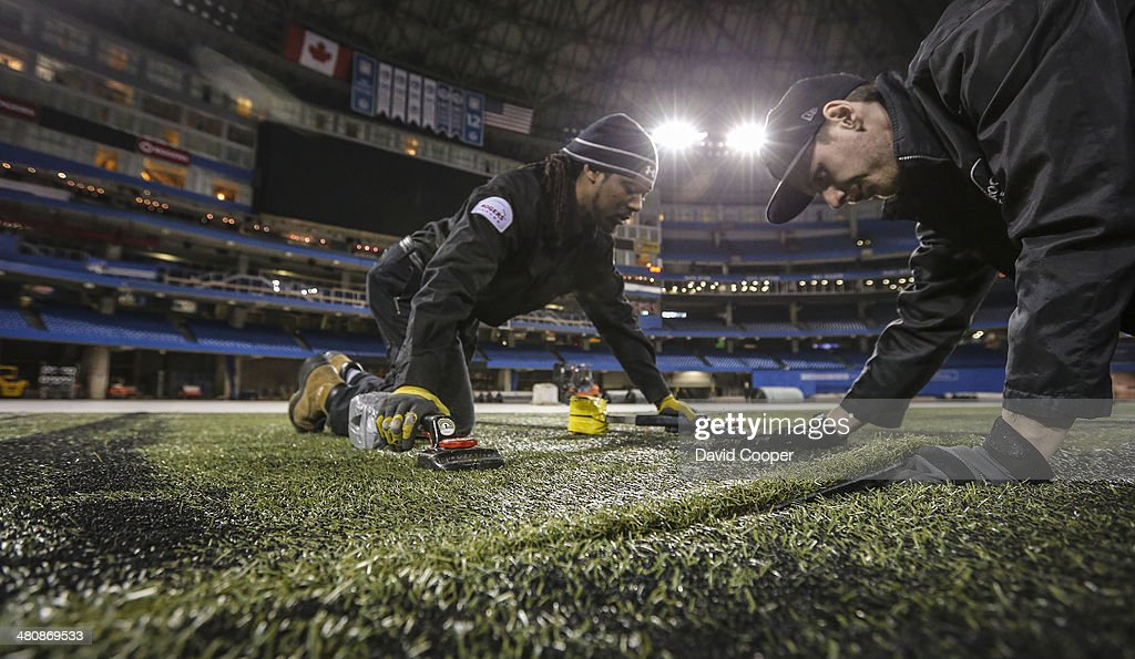 TORONTO, ON- MARCH 26 - The Baseball Turf is going back in at the Rogers Centre over the next two days. Field conversion technicians Mark Wade (left) and Steve Miller (right) adjust the seam between the carpets to get them just right. Let Spring really begin at the Rogers Centre March 26, 2014.