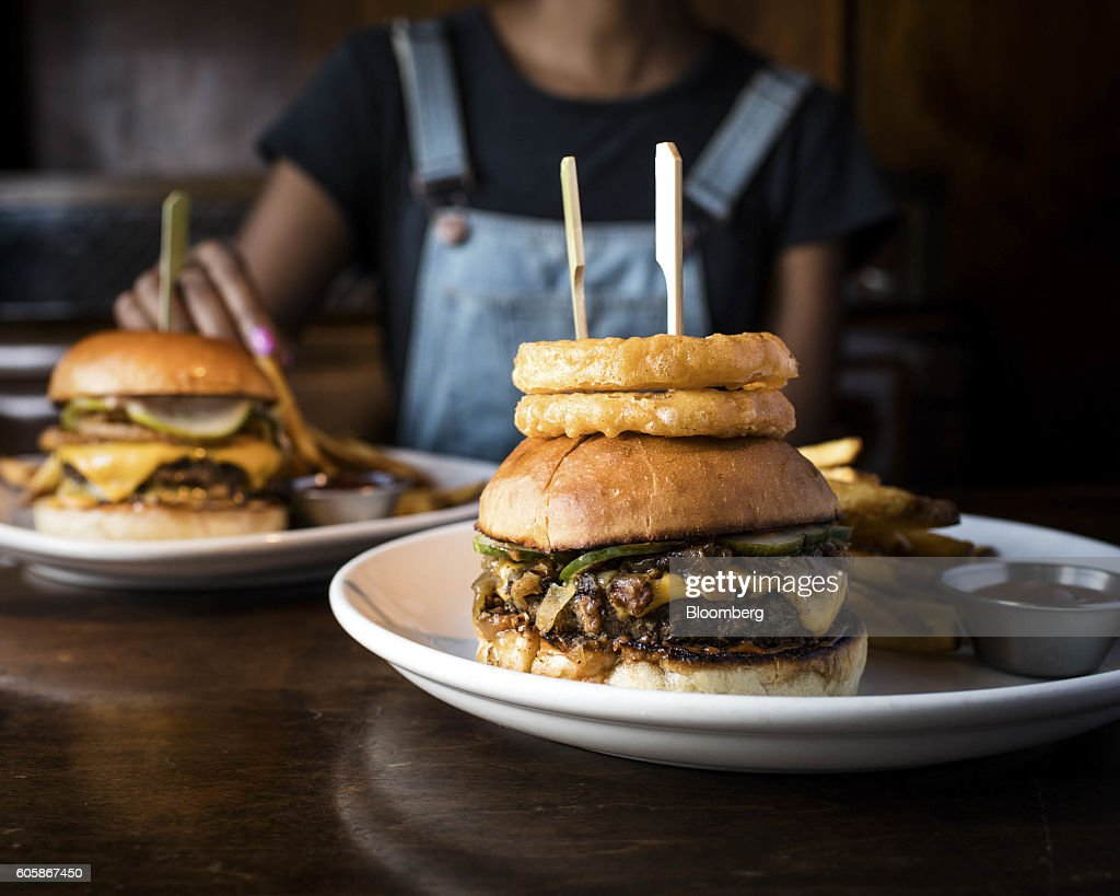 The Bash-Style Burger with fries is arranged for a photograph at Burger & Barrel restaurant in New York, U.S., on Monday, April 18, 2016. Top chefs pick their all-time favorites, from burgers with fat, mid-rare patties dripping with juice to thin, crisp disks of beef smothered with cheese. These are the ones the true masters crave when they're off duty. Photographer: Eric Medsker/Bloomberg via Getty Images