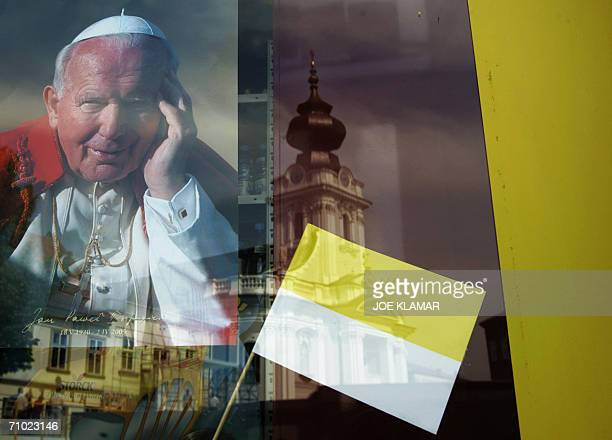 The Basilica of the Presentation of Virgin Mary church where late John Paul II was babtised is reflected on a shop window where a picture of the late...