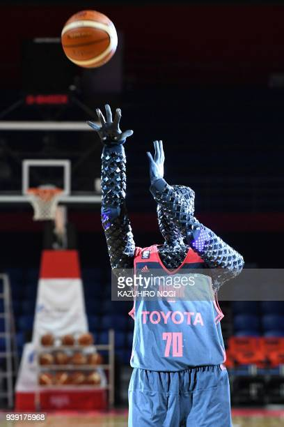 The basketballplaying robot named CUE shoots the ball during a halftime show rehearsal for a Japanese B League basketball match in Tokyo on March 28...