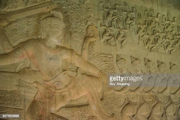 the bas-relief of the churning of the sea of milk shows vishnu in the centre, devas at the right, and apsaras and indra above. - khmer art stock photos and pictures