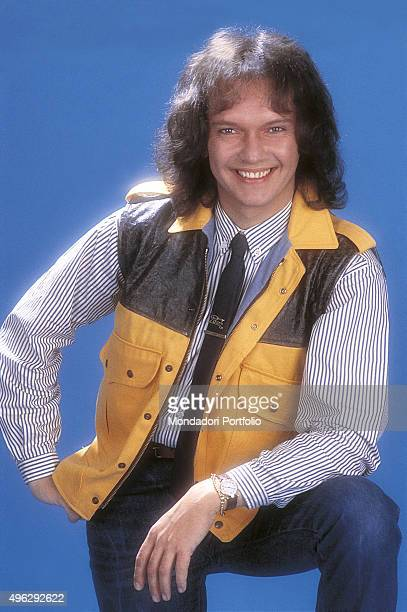The bass player and singer member of Italian band Pooh Red Canzian posing smiling for a photocall in a studio Italy 1982