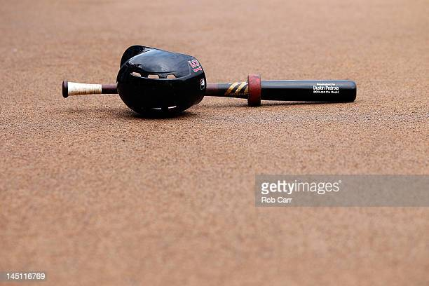 The bat and helmet of Dustin Pedroia of the Boston Red Sox sit on the ground before the start of the Red Sox and Baltimore Orioles game at Oriole...