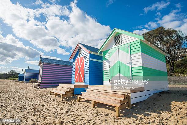 The bathing boxes on Dendy Street Beach with Middle Brighton pier and breakwater and the city skyline in the background.
