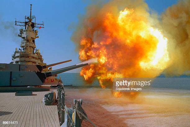 the battleship uss wisconsin (bb-64) fires a round from one of the mark 7 16-inch/50-caliber guns in turret no. 1 during operation desert storm.  the ship is firing at iraqi  targets in kuwait. - vilas_county,_wisconsin stock pictures, royalty-free photos & images