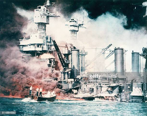 The battleships USS West Virginia and USS Tennessee sit low in the water and burn after the Japanese surprise attack on Pearl Harbor