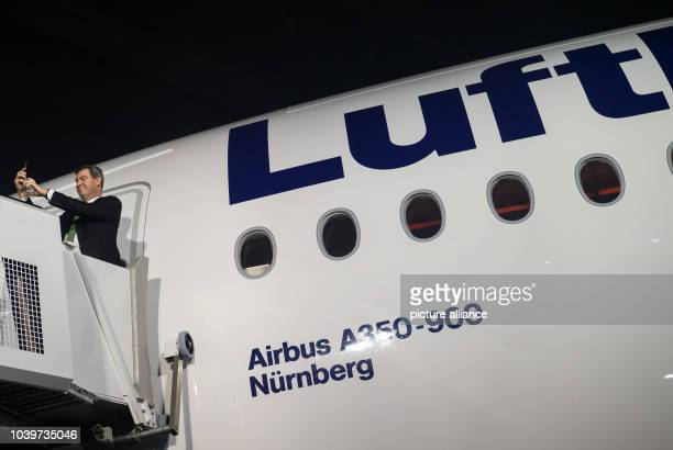The Bavarian Finance Minister Markus Soeder making a selfie with his smartphone in front of a new Lufthansa Airbus A350900 aircraft in Munich Germany...