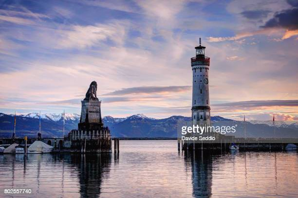 the bavarian lion monument and a lighthouse a the entrance of the seaport of lindau - bodensee stock-fotos und bilder