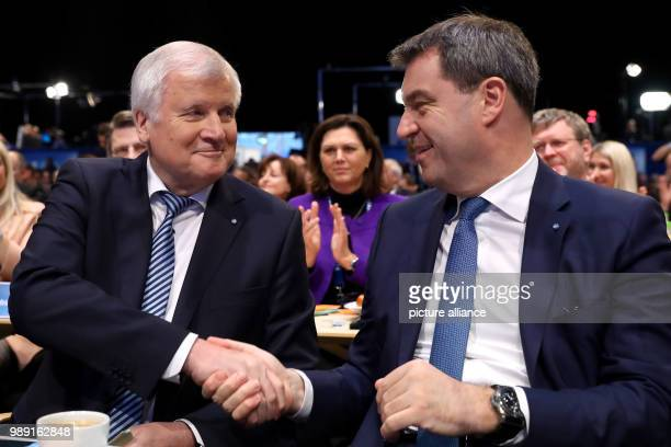 The Bavaria's Minister of Finance Markus Soeder congratulates Bavaria's state Premier and head of the Christian Social Union Horst Seehofer after his...