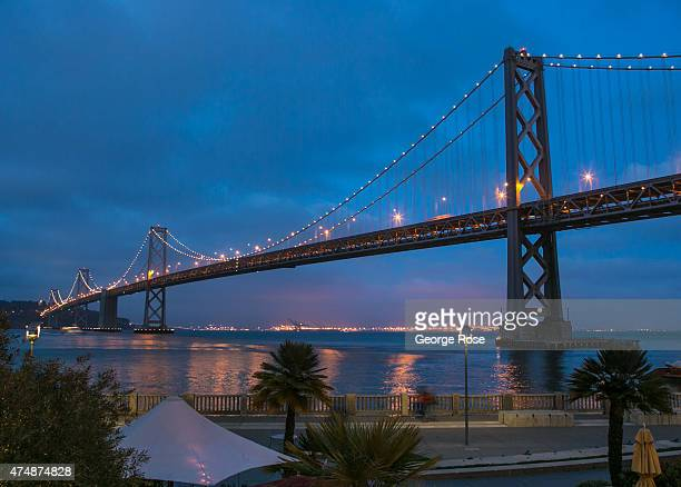 The Bay Bridge is a colorful evening backdrop along the Embarcadero as viewed from the Epic Roasthouse restaurant on May 8 in San Francisco...