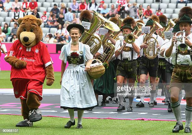 The Bayern Muenchen mascott walks in with a folk music group prior to the Bundesliga match between FC Bayern Muenchen and 1 FC Nuernberg at Allianz...