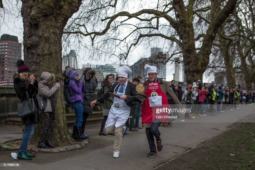 The BBC's Diplomatic correspondent James Landale (right) and MP Matt Warman (left) approach the first corner in the annual Parliamentary Pancake Race in Victoria Tower Gardens on Shrove Tuesday on February 13, 2018 in London, England. The annual Pancake Race, which raises money for the charity Rehab, sees teams of politicians and journalists racing around a circuit whilst tossing pancakes in frying pans. The team of journalists won this year's event.