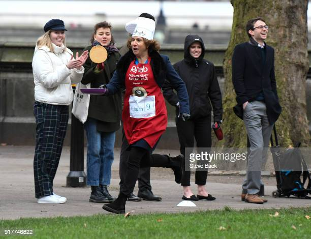 The BBC's Jo Coburn approachess the second corner in the annual Parliamentary Pancake Race in Victoria Tower Gardens on Shrove Tuesday on February 13...